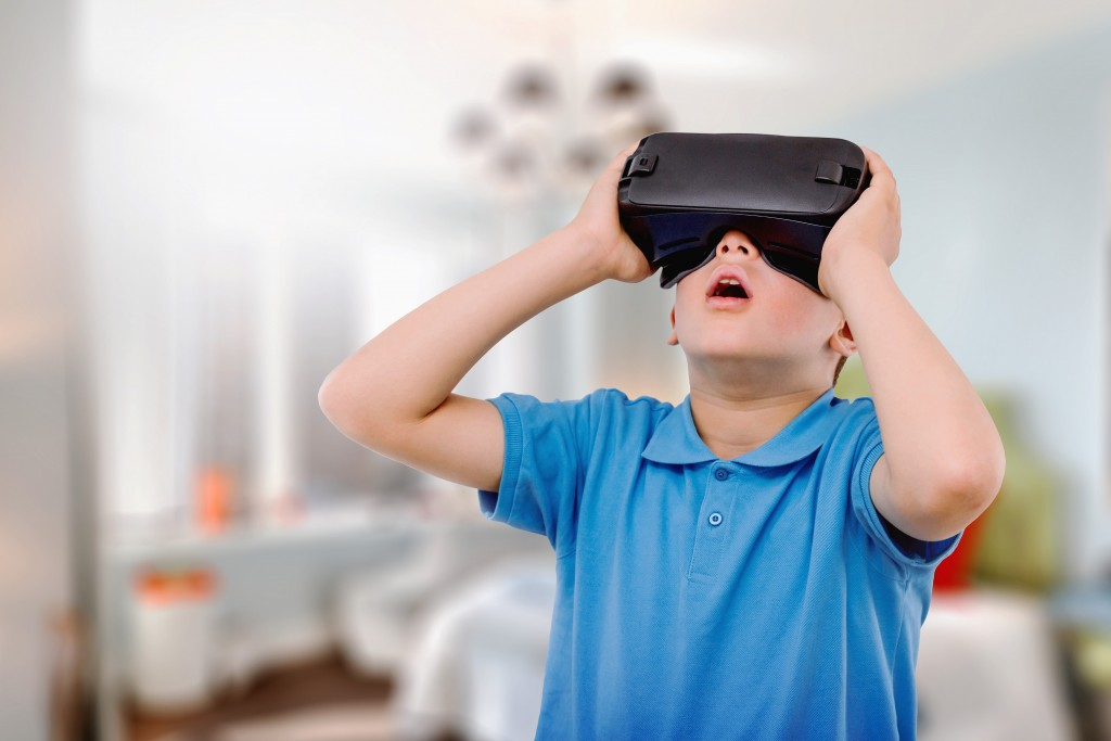 Amazed teen boy wearing virtual reality goggles watching